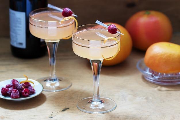 Cocktail au champagne avec jus de pamplemousse, garni de zeste et de framboises. style rustique.