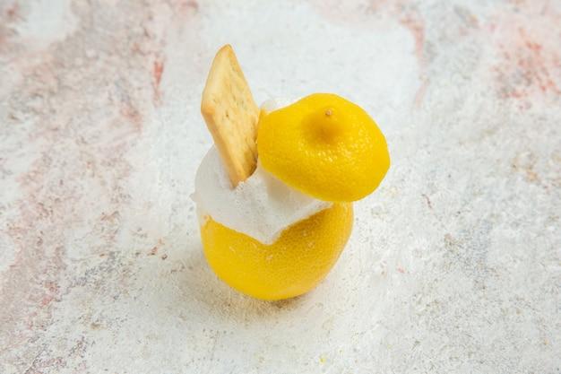 Cocktail au citron vue de face avec de la glace sur du jus de cocktail aux agrumes de table blanche