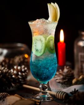 Cocktail au lagon bleu avec des tranches de glace, de kiwi et de pomme.