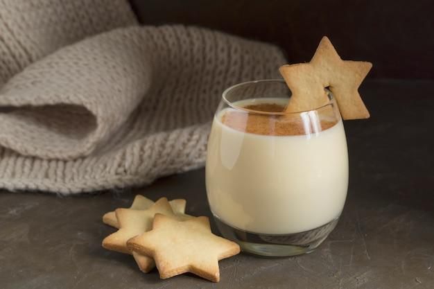 Cocktail au lait de poule et biscuits étoiles sur fond noir.