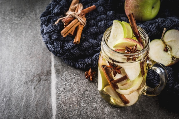 Cocktail d'automne. infusion de détoxication diététique avec pommes et épices - anis, cannelle. cocktail d'alcool au cidre de pomme. en pot de maçon sur une table en pierre noire. espace copie