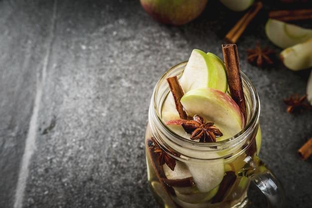 Cocktail d'automne. infusion diététique infusée d'eau aux pommes et épices anis, cannelle. cocktail d'alcool au cidre de pomme. en pot de maçon sur une table en pierre noire. fond