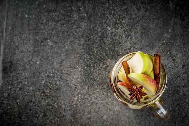 Cocktail d'automne. infusion diététique infusée d'eau aux pommes et épices anis, cannelle. cocktail d'alcool au cidre de pomme. en pot de maçon sur une table en pierre noire. vue de dessus