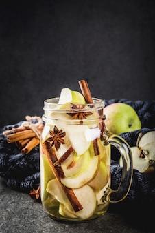 Cocktail d'automne. infusion diététique infusée d'eau aux pommes et épices anis, cannelle. cocktail d'alcool au cidre de pomme. en pot de maçon sur une table en pierre noire.