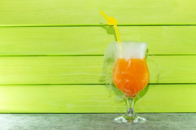 Cocktail à l'azote liquide. cocktail d'orange rafraîchissant d'été dans un bécher en verre avec une paille. à partir d'azote liquide