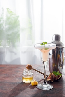 Cocktail bellini à la pêche et aux figues, miel sur fond clair au-dessus des fenêtres, espace copie