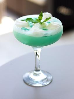 Cocktail bleu dans un beau verre avec crème glacée et feuilles de menthe verte