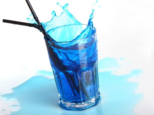 Cocktail bleu avec éclaboussures isolé sur blanc