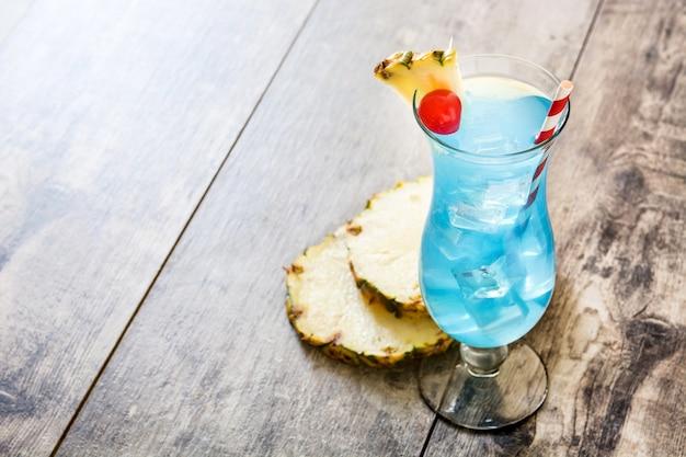 Cocktail bleu hawaïen sur une table en bois.