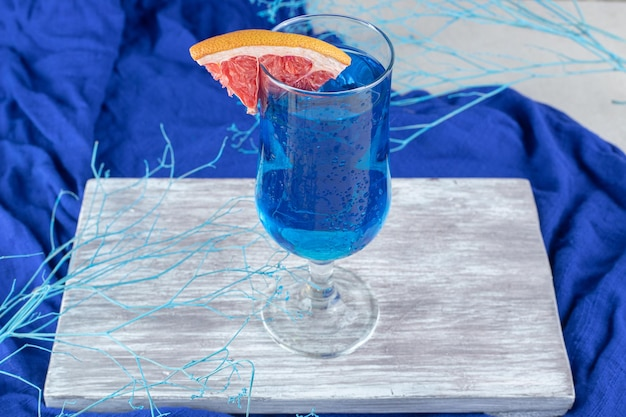 Cocktail bleu avec tranche de pamplemousse sur planche de bois