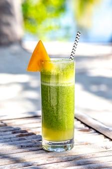 Cocktail de boisson d'été vert à la mangue sur la plage