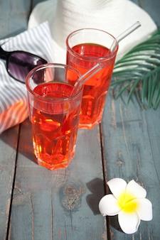 Cocktail de boisson rafraîchissante d'été sur le fond en bois. chapeau, lunettes de soleil et frangipanier plumeria à proximité.