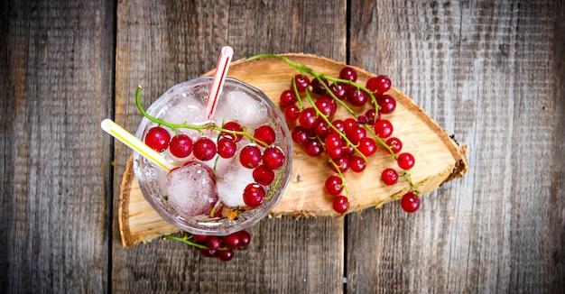 Cocktail de cassis. un cocktail de cassis sauvage avec de la glace sur une table en bois. vue de dessus