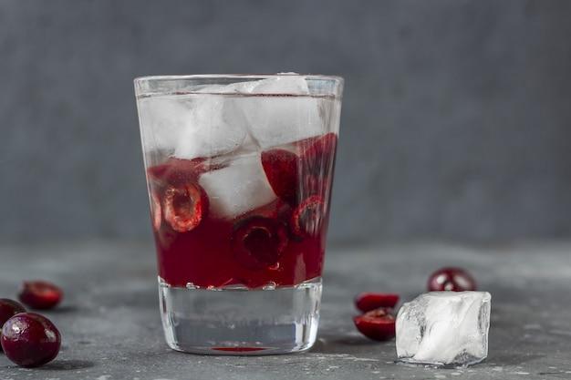 Cocktail de cerises fraîches. un cocktail avec du gin ou de la vodka, du sirop de cerise et des morceaux de cerise et de glace