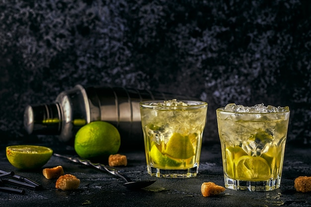 Cocktail de citron vert frais avec de la glace sur l'obscurité.