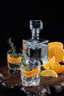 Cocktail classic dry gin avec tonique et zeste d'orange avec un brin de romarin sur une planche de bois avec des tranches d'orange juteuse