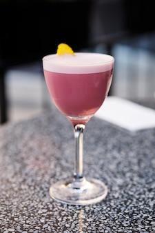 Cocktail de cognac à la cerise sur la table sur la terrasse extérieure (photo avec une faible profondeur de champ)