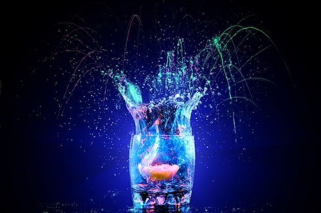 Cocktail coloré en verre avec éclaboussures et citron sur fond sombre. animation de club de fête. lumière mixte