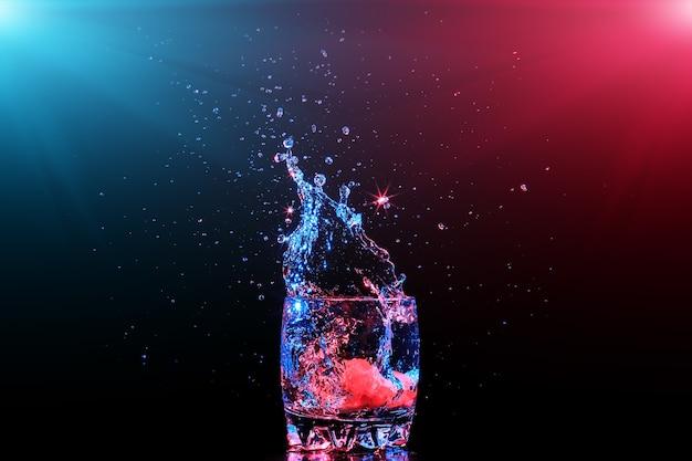Cocktail coloré en verre avec éclaboussures et citron sur fond sombre divertissement club de fête mélangé