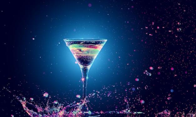 Cocktail coloré en verre avec splash sur fond sombre