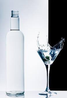 Cocktail contemporain classique avec éclaboussures et bouteille sur fond noir et blanc