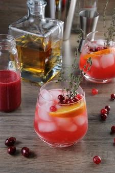 Cocktail cranberry orange bourbon smash avec une touche épicée de thym
