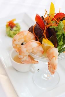 Cocktail de crevettes apéritif servi avec salade sur fond blanc