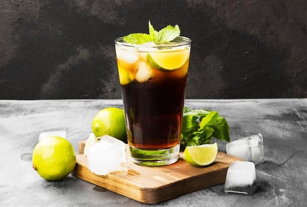 Cocktail cuba libre dans un verre sur un fond sombre. espace de copie. fond de nourriture