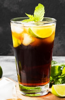 Cocktail cuba libre dans un verre sur un fond sombre
