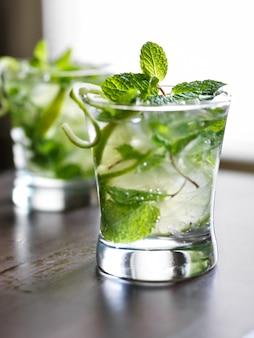 Cocktail - deux mojitos froids sur table en bois