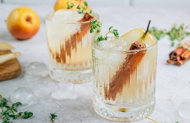 Cocktail épicé festif d'été aux poires et au thym sur fond beige clair.
