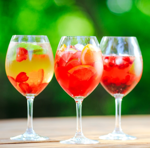 Cocktail d'été. cocktail de fruits sur vert. agrumes, baies, fraises, myrtilles, menthe, glace.