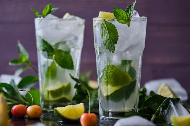 Cocktail d'été rafraîchissant mojito. ingrédients : glace, soda, rhum, sirop de sucre, citron vert, menthe.