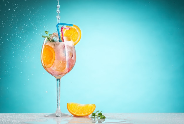 Le cocktail exotique à la rose et les fruits sur fond bleu