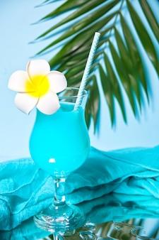 Cocktail exotique tropical curaçao bleu dans un verre avec fleur de frangipanier plumeria sous feuille de palmier.