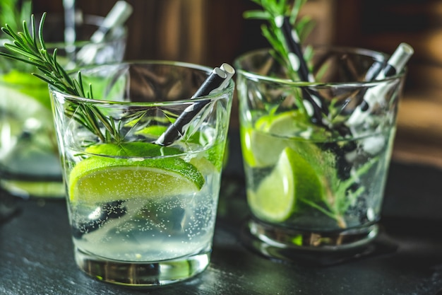 Cocktail frais au citron vert, glace et romarin, cocktail mojito à la fraise sur une table rustique