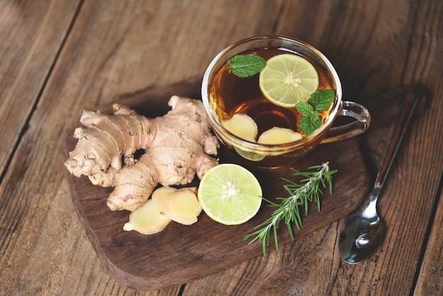 Cocktail frais au gingembre et au citron, jus de gingembre chaud en verre et tranches de thé au jus de racine de gingembre