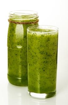 Cocktail frais sur isoler. un verre et une canette avec des cocktails de légumes.