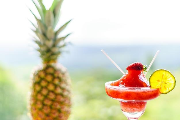 Cocktail de fraises à côté d'un pinaple avec une forêt en arrière-plan