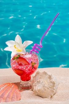 Cocktail de fraises sur la plage avec des coquillages
