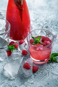 Cocktail de framboises, pétillant, limonade, thé glacé à la menthe fraîche sur fond de bois bleu. fermer.