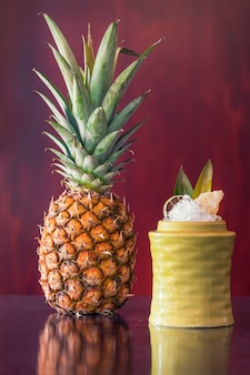 Cocktail de fruits à côté d'un ananas