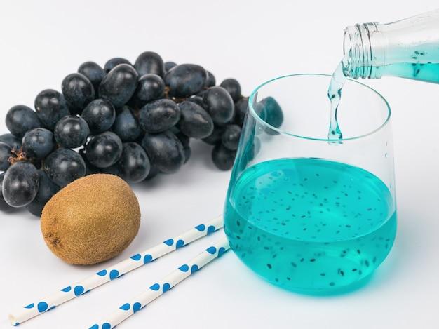Un cocktail de fruits exotiques est versé dans un verre et les fruits sont placés sur une table blanche. une boisson rafraîchissante exotique.