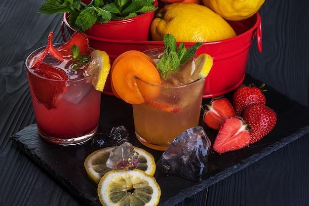 Cocktail De Fruits Avec Fruits Frais Et Glace. Dans Des Verres Sur Fond De Bois Noir Rustique Photo Premium