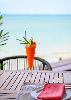 Cocktail de fruits mélangé avec citron vert et cerise sur une table en bois