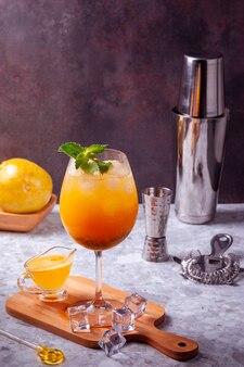 Cocktail de fruits de la passion sur une planche de cuisine avec des glaçons sur le sol, des fruits de la passion entiers, un shaker, une passoire et un doseur. copier l'espace