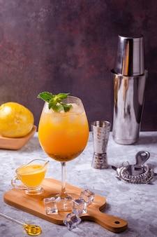 Cocktail de fruits de la passion servi dans un verre à vin sur une planche de cuisine avec des glaçons sur le sol, fond composé de fruits de la passion entiers, shaker, passoire et doseur. copier l'espace