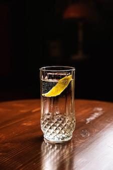 Cocktail gin tonic dans un verre highball servi sur glace, garniture au citron, à la table en bois du bar, avec espace pour copie.