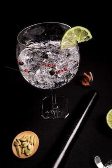 Cocktail de gin tonic sur fond noir avec des ingrédients