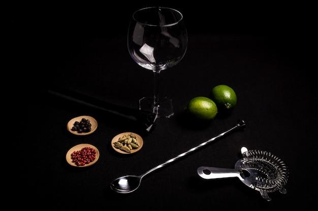 Cocktail de gin tonic sur fond noir avec ses ingrédients